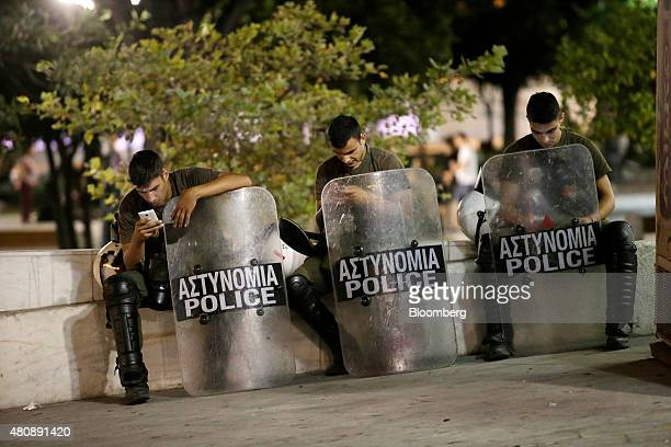 Riot police check their mobile phones while resting following clashes with antibailout protestors in central Athens Greece on Wednesday July 15 2015...