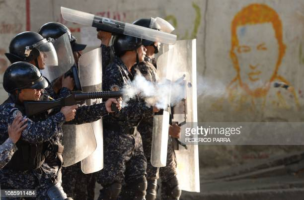 TOPSHOT Riot police clash with antigovernment demonstrators in the neighborhood of Los Mecedores in Caracas on January 21 2019 A group of soldiers...