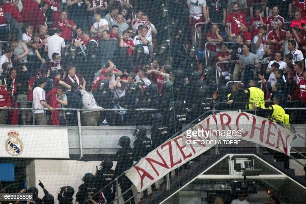 Riot police clash with Bayern fans in the tribunes during the UEFA Champions League quarterfinal second leg football match Real Madrid vs FC Bayern...