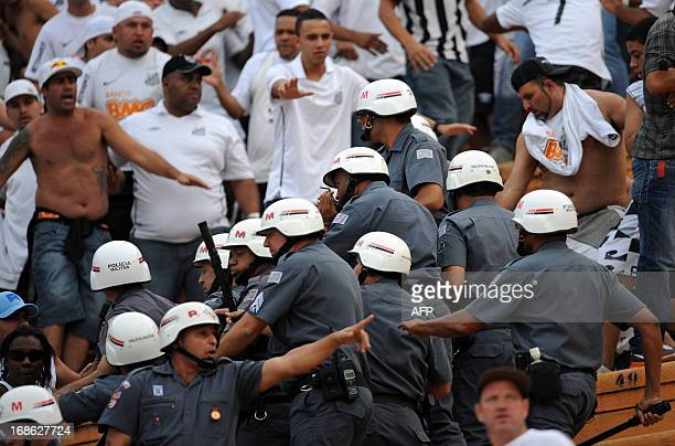 Riot police clash with fans of Santos FC during their 2013 Paulista championship first final football match against Corinthians held at Pacaembu...
