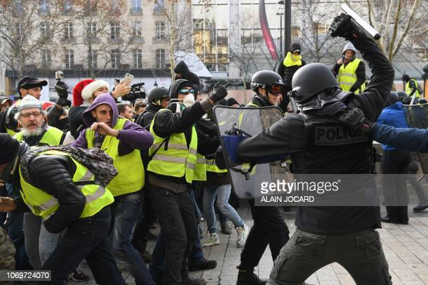 """Riot police clash with men wearing """"yellow vests"""" protestors on December 8, 2018 near the Arc de Triomphe in Paris during a protest against rising..."""