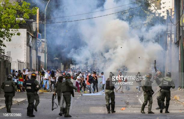 TOPSHOT Riot police clash with opposition demonstrators during a protest against the government of President Nicolas Maduro on the anniversary of the...