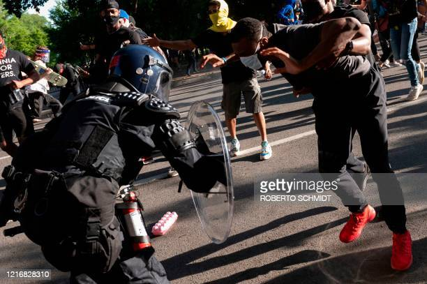 Riot police clashes with a protestor near the White House on June 1 2020 as demonstrations against George Floyd's death continue Police fired tear...