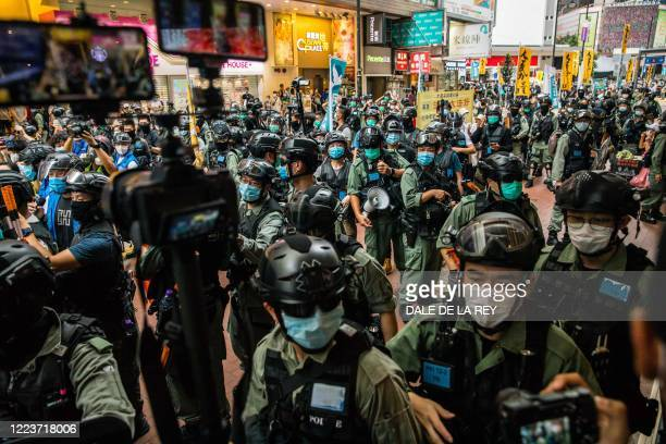 Riot police clear a street as protesters gathered to rally against a new national security law in Hong Kong on July 1 on the 23rd anniversary of the...