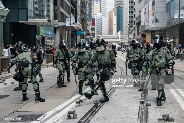 Riot police clear bricks on a street where protesters attempted to block traffic in Central district on November 14 2019 in Hong Kong China...