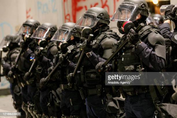 Riot police confront demonstrators gathered over the death of George Floyd an unarmed black man who died after being pinned down by a white police...