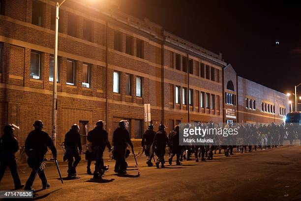 Riot police depart after forming a barricade and dispensing tear gas near the burned out CVS pharmacy the night after citywide riots over the death...