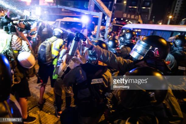 Riot police deploy pepper spray during a protest in the Mong Kok district of Hong Kong China on Sunday Oct 13 2019 A Hong Kong police officer was...