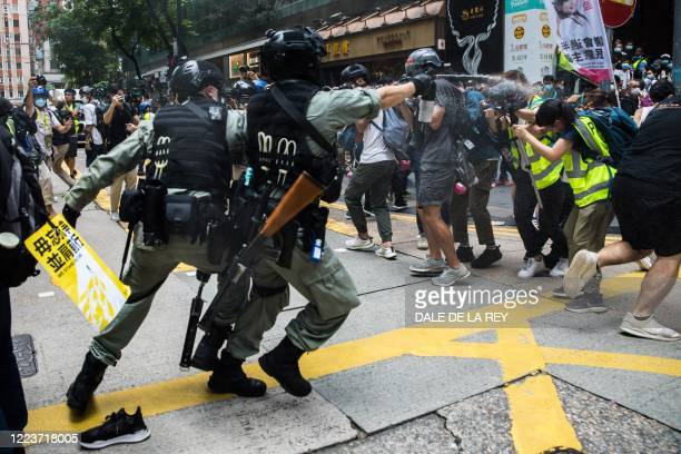 Riot police deploy pepper spray toward journalists as protesters gathered for a rally against a new national security law in Hong Kong on July 1 on...