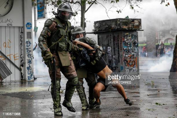 TOPSHOT Riot police detain a demonstrator as clashes erupted following a protest against the government of Chilean President Sebastian Pinera in...