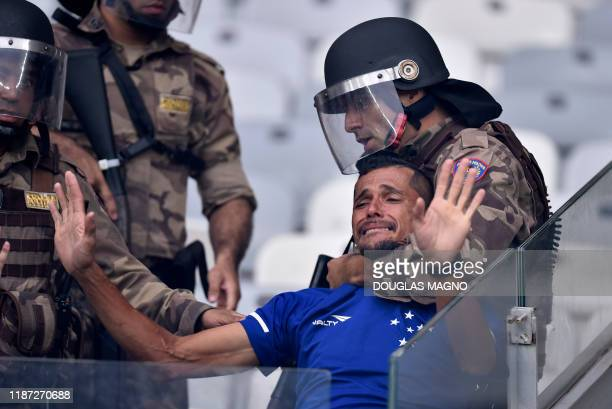 TOPSHOT Riot police detain a fan of Brazil's Cruzeiro as clashes erupted during the Brazilian Championship football match against Palmeiras in Belo...
