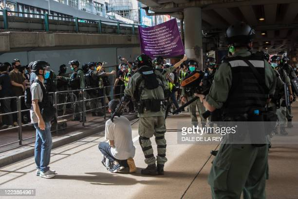 Riot police detain a man and display a flag warning people they may be committing an offence under a new national security law during a protest in...