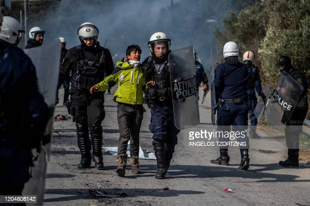 Riot police detain a migrant during clashes near the Moria camp for refugees and migrants, on the island of Lesbos, on March 2, 2020. - More than...
