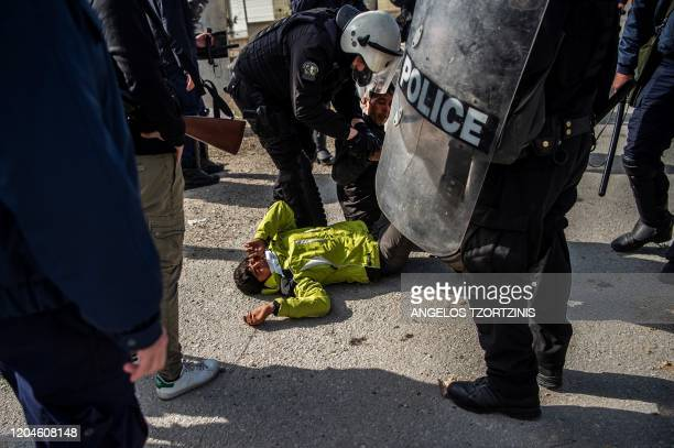 Riot police detain a migrant during clashes near the Moria camp for refugees and migrants on the island of Lesbos on March 2 2020 More than 13000...