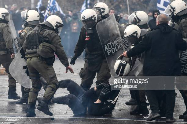 Riot police detain a protester during a demonstration against the agreement with Skopje to rename neighbouring country Macedonia as the Republic of...