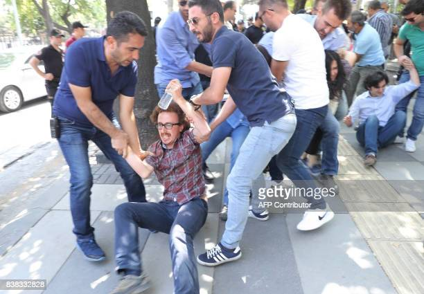 Riot police detain a protester during a protest against the detention of hungerstriking teacher Semih Ozakca and literature professor Nuriye Gulmen...