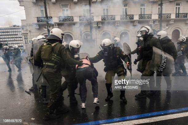Riot police detain a protester during clashes with riot police during a demonstration against the agreement with Skopje to rename neighbouring...