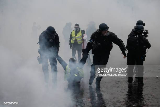 TOPSHOT Riot police detain a protester during clashes with Yellow vests protesters demonstrating against rising oil prices and living costs on...