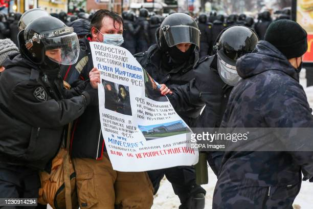 Riot police detain a protester holding a placard during the demonstration in support of the opposition political leader Alexei Navalny. Hundreds of...