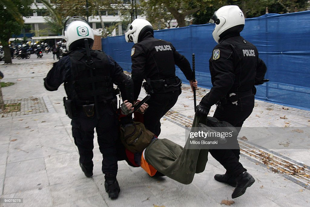 Riot police detain a protestor during a demonstration commemorating the fatal shooting of 15-year-old Alexandros Grigoropoulos' by police a year ago, on December 6, 2009 in central Athens, Greece. Two police officers will go on trial in the new year for the murder of Grigoropoulos.