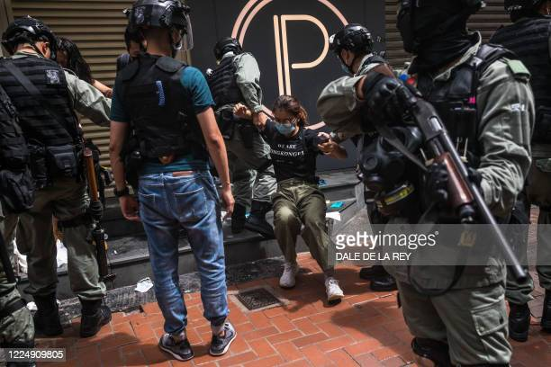 Riot police detain a woman as they clear protesters taking part in a rally against a new national security law in Hong Kong on July 1 on the 23rd...