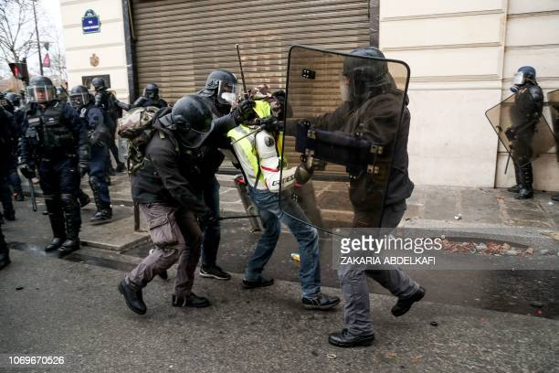 TOPSHOT Riot police detain a yellow vest protestor on December 8 2018 near the Champs Elysees in Paris during a protest against rising costs of...
