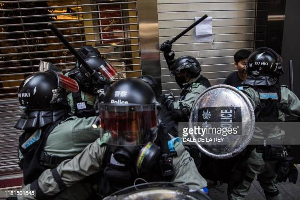 TOPSHOT Riot police detain two men in the Central district of Hong Kong on November 11 2019 A Hong Kong policeman shot a masked protester in the...
