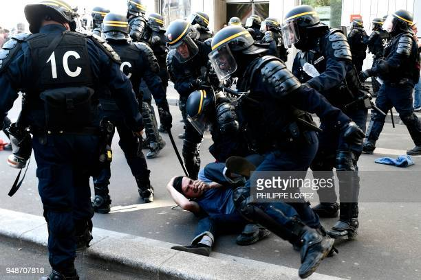TOPSHOT Riot police detains a protester during clashes on the sidelines of a demonstration on April 19 2018 in Paris as part of a multi branch day of...