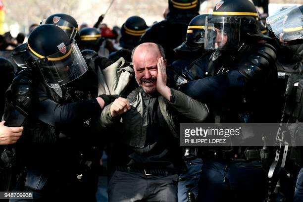 Riot police detains a protester during clashes on the sidelines of a demonstration on April 19 2018 in Paris as part of a multi branch day of protest...