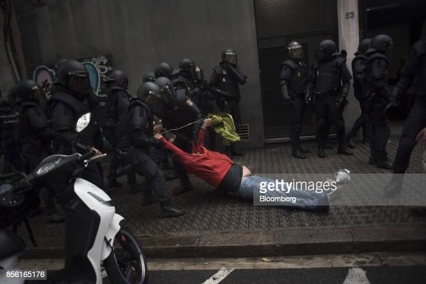 Riot police drag a member of the public away from a school being used as a polling station for the banned referendum in Barcelona Spain on Sunday Oct...