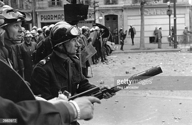 Riot police draw up their barricades during the student riots in Paris and prepare to fire tear gas on the crowds
