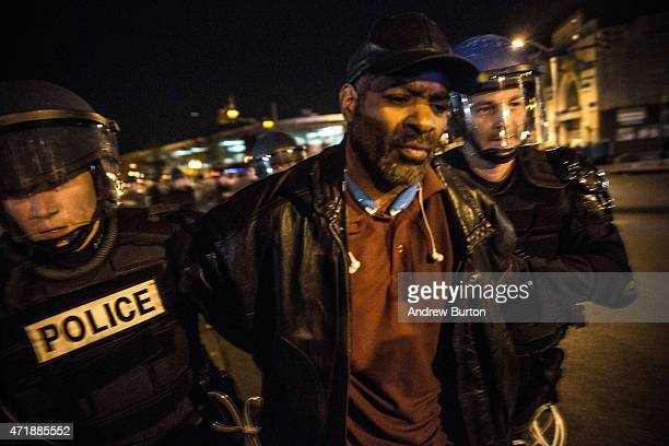 Riot police enforce a 10PM curfew and arrest a man on the same day that Maryland state attorney Marilyn J Mosby announced that charges would be filed...