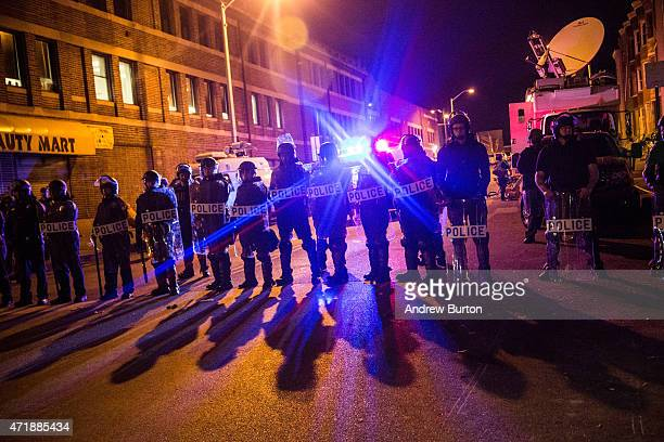 Riot police enforce a 10PM curfew and clear the streets of protesters and media on the same day that Maryland state attorney Marilyn J Mosby...