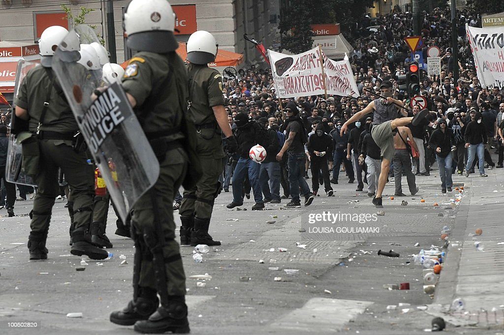 Riot police faces demonstrators during a massive demonstration on May 5, 2010 in Athens.Three people were killed in a firebomb attack on a bank in central Athens on May 5 and around 20 people were evacuated from the building.