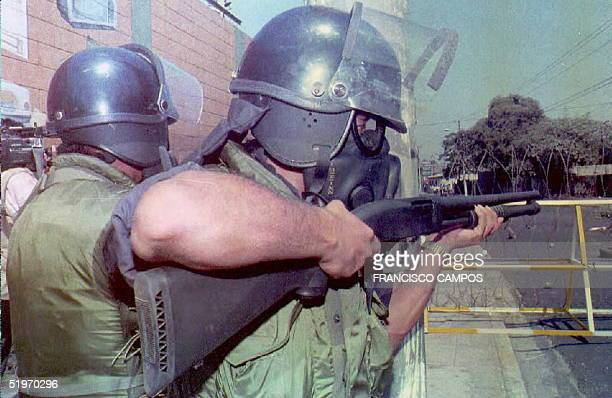 Riot police fire rubber bullets 14 February at former army troops demonstrating in front of the presidential palace in San Salvador A dozen people...