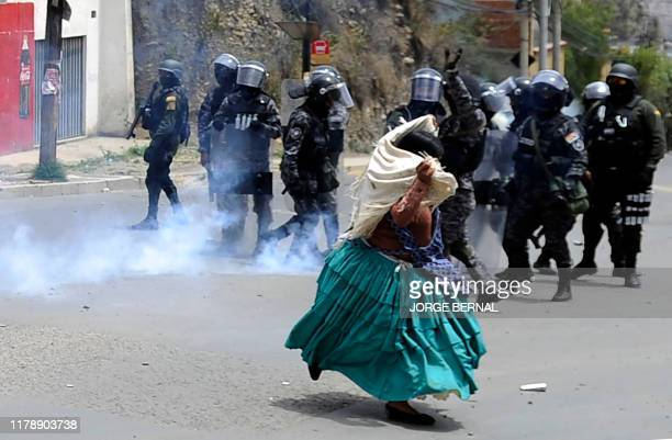 Riot police fire tear gas as an indigenous woman protests against a civic strike triggered by the result of the October 20 election run away from...