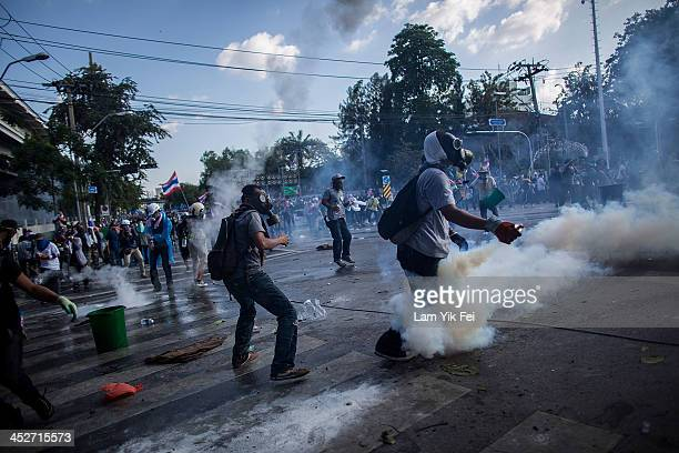 Riot police fire tear gas as antigovernment protesters try to remove a barricade and occupy the government house on December 1 2013 in Bangkok...