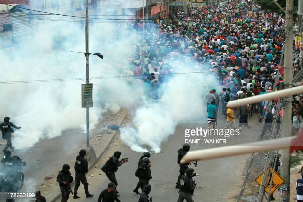 Riot police fire tear gas as supporters of the Movimiento Al Socialismo party, of Bolivian President Evo Morales, confront supporters of the...