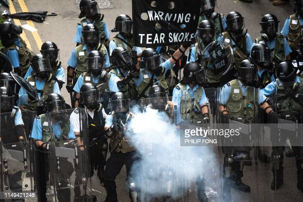 TOPSHOT Riot police fire tear gas during clashes with protesters during a rally against a controversial extradition law proposal outside the...