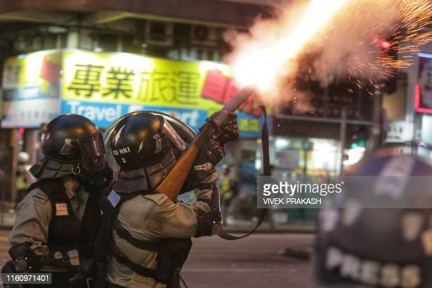 TOPSHOT Riot police fire tear gas towards prodemocracy protesters during a standoff in the Wan Chai district in Hong Kong on August 11 2019 Thousands...