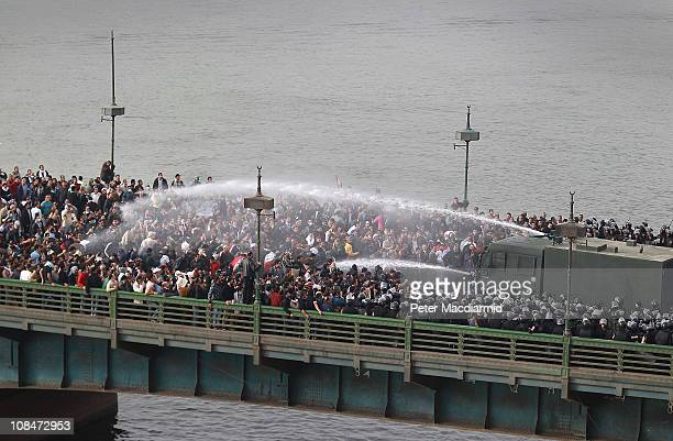 Riot police fire water cannons at protestors attempting to cross the Kasr Al Nile Bridge on January 28, 2011 in downtown Cairo, Egypt. Thousands of...