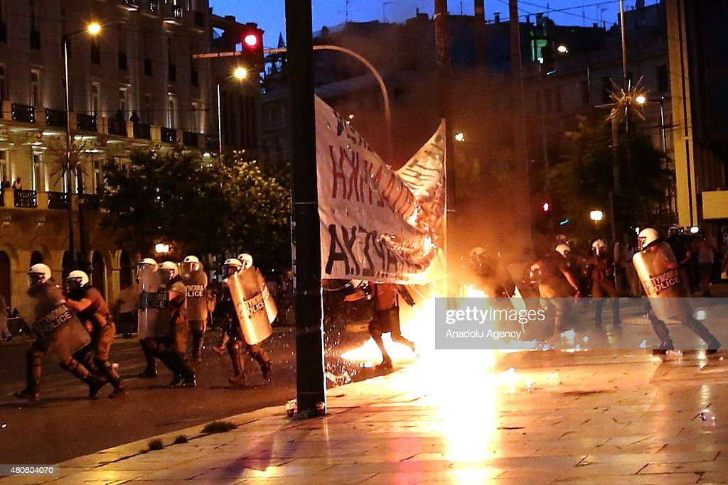 Riot police forces clash with protesters in front of the Greek Parliament during an anti-austerity demonstration in Athens on July 15, 2015 while Greek MPs debate the economic reform measures in the bailout agreement. Riot police responded with tear gas against dozens of anti-austerity protesters who set ablaze parts of Syntagma square in central Athens.