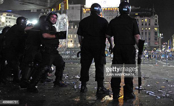 Riot police guard a fast food store during the celebration of Boca Juniors fan's day at the Plaza de la Republica square in Buenos Aires Argentina on...