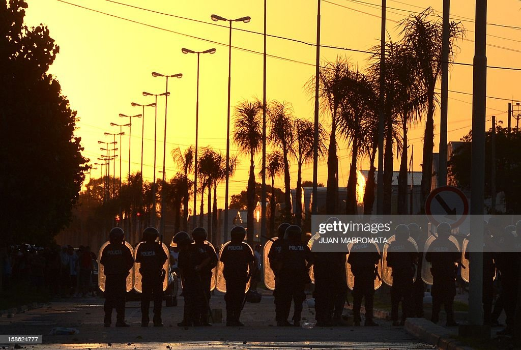 Riot police guard a supermarket in San Fernando, Buenos Aires province on December 21, 2012. Two people died Friday and two more were seriously injured as mobs looted supermarkets in Rosario, Argentina's third largest city, an official said. A series of lootings have taken place in five other cities of Argentina since Thursday leaving also near a hundred people injured and 300 detained.