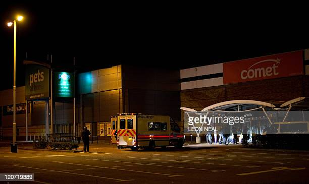 Riot police guard an electronics superstore on a retail park after a breakin in Enfield north London on 7 August 2011 Two police cars and a large...