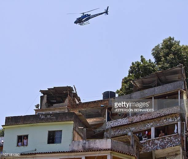 A riot police helicopter flies over the Morro do Alemao shantytown during the raid on November 28 2010 in Rio de Janeiro Brazil After days of...