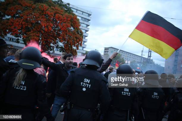 Riot police hold back right-wing supporters shouting abuse at leftists nearby the day after a man was stabbed and died of his injuries on August 27,...