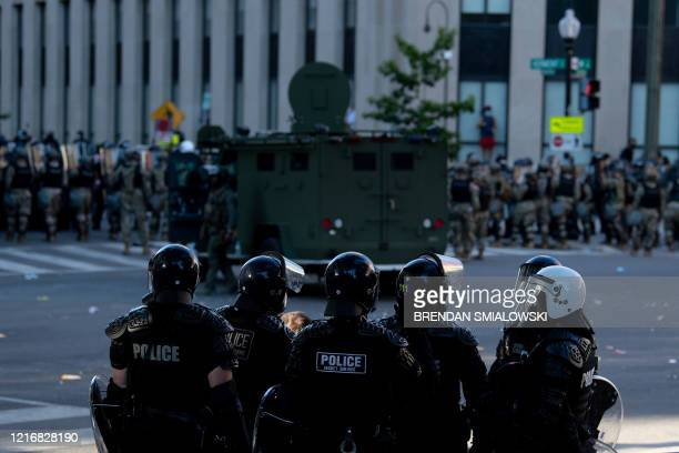 Riot police hold people back as US President Donald Trump visits St John's Church after the area was cleared of people protesting the death of George...