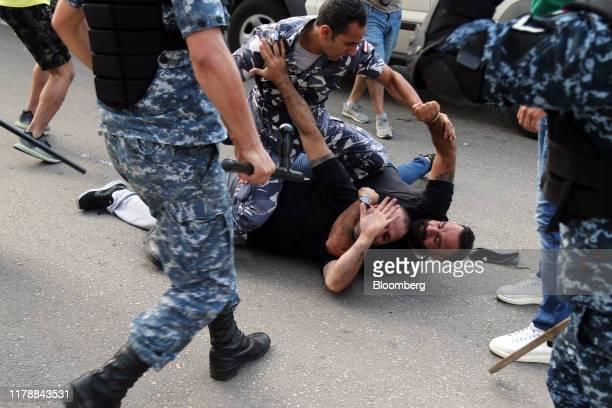 Riot police intervene as an antigovernment protester tackles an Hezbollah supporter during clashes with antigovernment protesters in Beirut Lebanon...