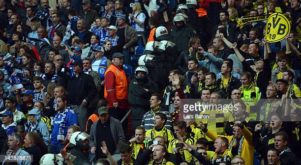 Riot police is seen between fans of Schalke and Dortmund during the Bundesliga match between FC Schalke 04 and Borussia Dortmund at Veltins Arena on...